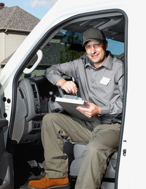 photo of a mover sitting in his van signing documents