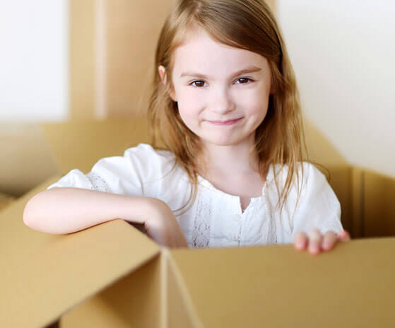 photo of a smiling girl comming out of a moving box